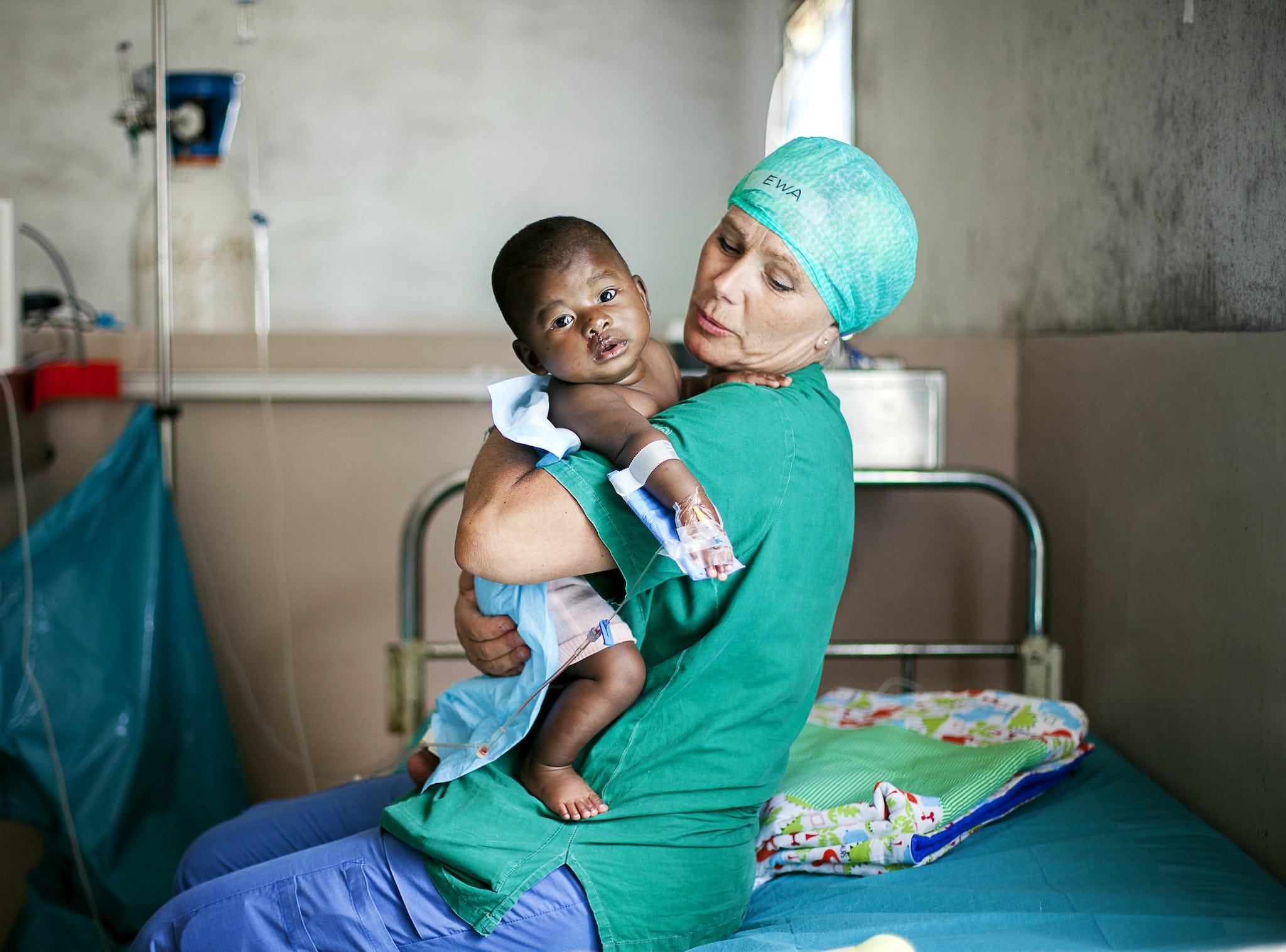 operation smiles volontär håller ett barn i famnen efter operation