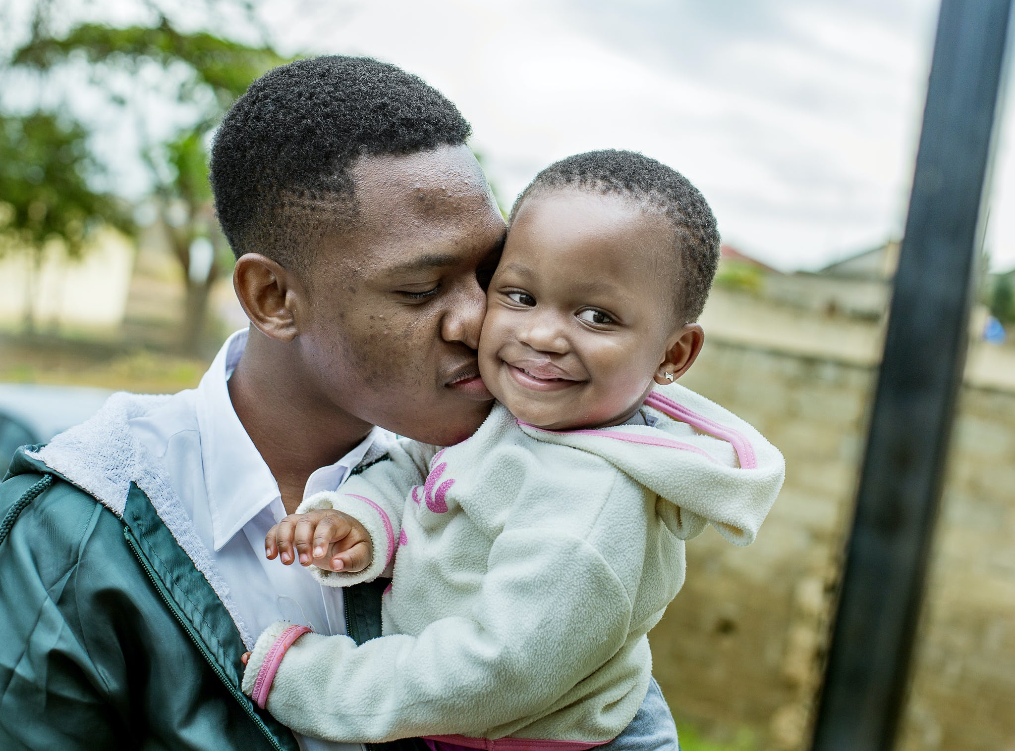 glad tjej i sin pappas famn under operation smiles uppdrag